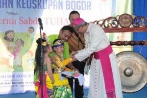 Dua anak kecil menghantar pemukul gong kepada Bapa Uskup Mgr. Paskalis Bruno Syukur, OFM